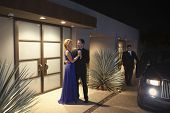 Rich couple dancing by doorway of house ready to leave at night
