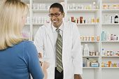 Happy middle aged male pharmacist giving prescription to the customer at workplace