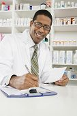 Portrait of a happy African American pharmacist writing prescription with medicines in the background