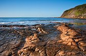 Kimmeridge Bay Seascape With Rock Ledges Extending Out To Sea On Blue Sky Day