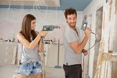 Happy young couple having fun during renovation, playing with power drill.