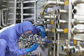 Industrial details - Technician in blue,protective uniform,mask and goggles fixing valves in plant