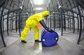 totalmente protegidos no uniforme amarelo, máscara e técnico de luvas de borracha, rolando o barril com su tóxico