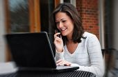 stock photo of online education  - Young woman talking on cell phone and using laptop - JPG