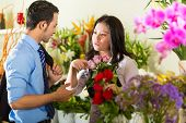 Friendly Asian florist or Saleswoman in a flower shop advises a customer