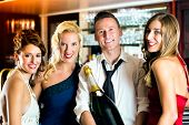 Good friends - bartender and women - with a large magnum bottle champagne at bar having fun