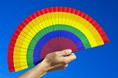 someone holding a hand fan painted with the colors of the gay pride flag over the blue sky