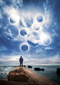 Abstract Space Fantasy Illustration. Man Starring At The Glowing Planet Spheres In Dramatic Blue Sky