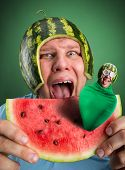 Scared man with watermelon helmet trying to eat slice with parasitic caterpillar in it