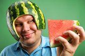 Bizarre man in a helmet from a watermelon preparing to eat