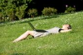 Girl With A Laptop Relaxing On The Grass