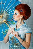 Geisha In A Smart Dress With Umbrella