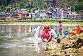 POKHARA,NEPAL-MAY 25:Family washing cloth in Fewa lake on May 25, 2013, Pokhara,Nepal.One of the mos