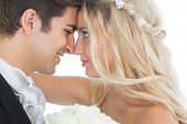 foto of white gown  - Happy young married couple looking each other in the face on white background - JPG