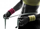 close up  one  woman exercising fitness measuring with tape measure in silhouette  on white backgrou