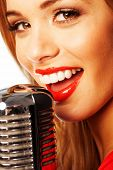 Close up portrait of a beautiful young female vocalist wearing bright red lipstick singing into a mi