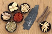 image of qi  - Acupuncture needles with chinese herbal medicine selection over bamboo - JPG