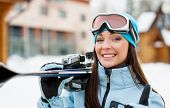 Close up of woman wearing sports jacket and goggles who hands skis and thumbs up
