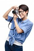 Woman in spectacles makes photos with retro photographic camera, isolated on white