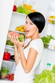 Woman eats watermelon near the opened refrigerator full of vegetables and fruit. Concept of healthy and dieting food