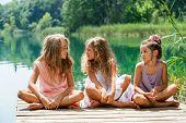 Three Girl Friends Sitting On Jetty At Lake.