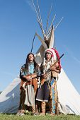 pic of wigwams  - Two North American Indians stand near a wigwam - JPG