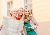 holidays and tourism concept - beautiful blonde women with tourist map in the city