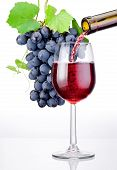 stock photo of flux  - Pouring a glass of red wine and bunch of grapes with leaves isolated on white background - JPG