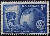 United States Of America - Circa 1955: Stamp Printed In Usa, Shows Torch Globe And Rotary Emblem