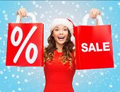 shopping, sale, gifts, christmas, x-mas concept - smiling woman in red dress and santa helper hat with shopping bags