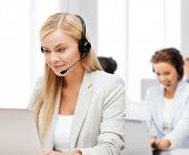 business, call centre and technology concept - female helpline operator with headphones and laptop p