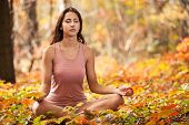 pic of crossed legs  - Beautiful young girl meditating in autumn park - JPG