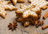 stock photo of ginger bread  - Snowflake shaped gingerbread cookies stacked and tied with a gold bow - JPG