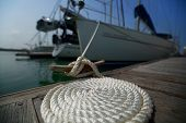 Coil of the rope on the wooden pier tied up to the yacht. Focus on the coil.