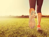 picture of sunrise  -  an athletic pair of legs on grass during sunrise or sunset  - JPG