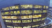 Employees on workplaces at evening in office building. View from unmanned quadrocopter