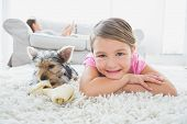 stock photo of puppies mother dog  - Little girl lying on rug with yorkshire terrier smiling at camera at home in the living room - JPG