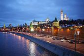 Traffic on Kremlin embankment against Ivan Great bell tower and Grand Kremlin Palace at evening in M