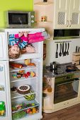 Little girl sits in freezer refrigerator in the kitchen at inverted house