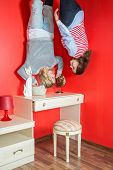 Two women upside down in the bedroom above the dressing table