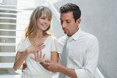 Happy young woman showing engagement ring to man at home
