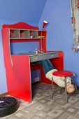 Little girl in children room under the chair at inverted house