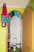 Two children upside down on the ceiling near toilet at inverted house