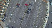Some cars on big parking in courtyard among buildings. Aerial view