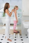 Side view of a woman braiding cute little girl's hair in the bathroom at home