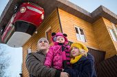 Family of three against the inverted house with red car