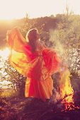 Beautiful witch in the woods near the fire. Magic woman celebrating Halloween. Girl doing witchcraft