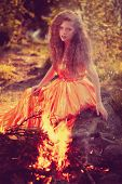 Beautiful witch in the woods near the fire. Magic woman celebrating Halloween. Girl doing witchcraft in the forest.