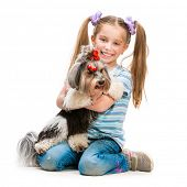 Happy smiling little girl is with her dog Yorkshire Terrier isolated on white
