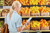 Girl looks through shopping list near the pile of fruits lying in the braided baskets in the store